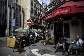 People have lunch at the extended terrace of a restaurant made of wooden pallets in Paris on July 23, 2020, in respect for social distancing due to the COVID-19 coronavirus pandemic. (Photo by Christophe ARCHAMBAULT / AFP) (Photo by CHRISTOPHE ARCHAMBAULT/AFP via Getty Images)