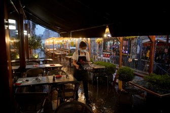 PARIS, FRANCE - SEPTEMBER 23: A waiter clears tables on a terrace of a Paris restaurant as the French Government announced that from Monday all bars and cafes in Paris will be made to shut at 10pm as part of a string of new measures to curb the spread of Covid-19 in France on September 23, 2020 in Paris, France. With the rise in Coronavirus cases in France at 204 per 100,000 inhabitants, the French Government have followed other governments in introducing new restrictions aimed at reducing the spread of Covid-19 whilst avoiding another national lockdown. In large cities, including Paris, gatherings will be limited to ten people in public spaces, bars to close at 10 p.m., local and student parties will be prohibited. (Photo by Kiran Ridley/Getty Images)