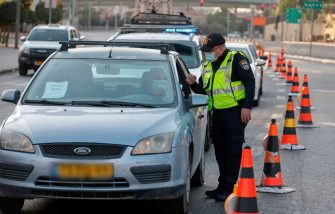 An Israeli policeman inspects a driver's papers at a checkpoint in Jerusalem, on September 19, 2020, to enforce lockdown after a spike in COVID-19 cases. - Israel imposed a second nationwide lockdown to tackle one of the world's highest coronavirus infection rates, despite public protests over the new blow to the economy. The three-week shutdown from yesterday just hours before Rosh Hashana, the Jewish New Year, and will extend through other key religious holidays, including Yom Kippur and Sukkot. (Photo by MENAHEM KAHANA / AFP) (Photo by MENAHEM KAHANA/AFP via Getty Images)