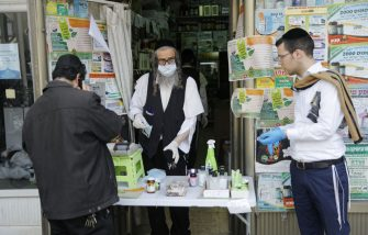 An ultra-Orthodox Jewish man wearing protective gloves and mask sells products at the door of a pharmacy, in the religious Israeli city of Bnei Brak, near Tel Aviv, on April 6, 2020, during the novel coronavirus pandemic crisis. - More than 7,000 cases of COVID-19, including 40 deaths, have been officially declared in Israel, half of which according to local media, are ultra-Orthodox Jews, prompting the Prime Minister on April 3, to give a green light for amry deployment in the city, considered the centre of the country's novel coronavirus outbreak. (Photo by MENAHEM KAHANA / AFP) (Photo by MENAHEM KAHANA/AFP via Getty Images)