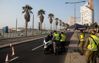 TEL AVIV, ISRAEL - SEPTEMBER 18:  Police officers stop a motorcycle at a road block as Israel enters a new lockdown on  September 18, 2020 in Tel Aviv, Israel. As the country grapples with a surge in Covid-19 cases it has imposed a three-week lockdown that coincides with Rosh Hashanah, the Jewish new year, and Yom Kippur, the Day of Atonement.  (Photo by Amir Levy/Getty Images)