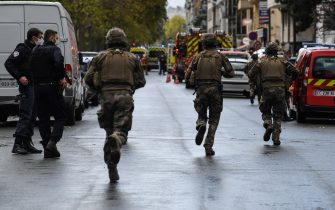 TOPSHOT - French soliders rush to the scene after several people were injured near the former offices of the French satirical magazine Charlie Hebdo following an alleged attack by a man wielding a knife in the capital Paris on September 25, 2020. - The threats coincide with the trial of 14 suspected accomplices of the perpetrators of the massacres at Charlie Hebdo and a Jewish supermarket that left a total of 17 dead. (Photo by Alain JOCARD / AFP) (Photo by ALAIN JOCARD/AFP via Getty Images)
