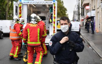 A French police officer stands guard as firefighters lift an injured person into an ambulance near the former offices of the French satirical magazine Charlie Hebdo following an alleged attack by a man wielding a knife in Paris on September 25, 2020. - The threats coincide with the trial of 14 suspected accomplices of the perpetrators of the massacres at Charlie Hebdo and a Jewish supermarket that left a total of 17 dead. (Photo by Alain JOCARD / AFP) (Photo by ALAIN JOCARD/AFP via Getty Images)