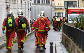 French firefighters move an injured person into an ambulance near the former offices of the French satirical magazine Charlie Hebdo following an alleged attack by a man wielding a knife in Paris on September 25, 2020. - The threats coincide with the trial of 14 suspected accomplices of the perpetrators of the massacres at Charlie Hebdo and a Jewish supermarket that left a total of 17 dead. (Photo by Alain JOCARD / AFP) (Photo by ALAIN JOCARD/AFP via Getty Images)