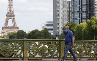 """A man wears a protective face mask while walking across Pont Mirabeau bridge, near the Eiffel Tower, on August 27, 2020, in Paris. - France's prime minister on August 27 announced face masks will become compulsory throughout Paris, expressing concern over an """"undeniable"""" trend of expanding coronavirus infection in the country. (Photo by Ludovic MARIN / AFP) (Photo by LUDOVIC MARIN/AFP via Getty Images)"""