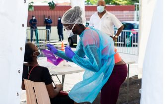 TOPSHOT - A person has a PCR test carried out at an open air clinic testing for the novel coronavirus, Covid-19, in Capesterre-Belle-Eau on the French Carribean archipelago of Guadeloupe on September 23, 2020. (Photo by Lara  BALAIS / AFP) (Photo by LARA  BALAIS/AFP via Getty Images)