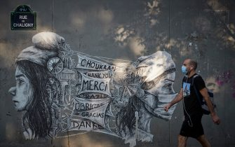 PARIS, FRANCE - SEPTEMBER 22: A Parisian walks past street art by Ardif on the corner of Saint-Anthoine Hospital in Paris, thanking Hospital workers for their work under Covid-19 pandemic, as hospitals in France initiate â  plan blancâ   to cope with the second wave spike in severe Covid-19 cases and hospital admissions in France on September 22, 2020 in Paris, France. In Paris region, one of the most affected areas in France, the number of outbreaks of contamination varies daily, with 18 new clusters reported in the past week. The exponential rise in reported cases in France, it is the 20 to 30 year-olds who are currently most strongly affected by the coronavirus epidemic. (Photo by Kiran Ridley/Getty Images)
