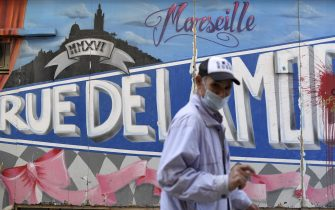 A man wearing a face mask  walks in front of a graffito  in Marseille, southeastern France, on September 14, 2020, amid the Covid-19 pandemic, caused by the novel coronavirus. (Photo by NICOLAS TUCAT / AFP) (Photo by NICOLAS TUCAT/AFP via Getty Images)