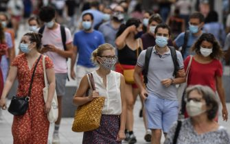 People with protective mask walk on a pedestrian street in Lyon on August 22, 2020 on the first day of mandatory mask wearing in parts of city centre. - Masks are obligatory to curb the spread of COVID-19 disease caused by the novel coronavirus in France in open areas of some cities as well as on public transport and in enclosed spaces such as shops, banks and government offices. (Photo by PHILIPPE DESMAZES / AFP) (Photo by PHILIPPE DESMAZES/AFP via Getty Images)