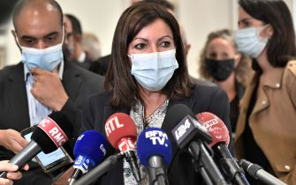 """Paris mayor Anne Hidalgo, wearing a protective face mask, answers journalists' questions at the """"Tribunal de Paris"""" courthouse in Paris, on September 21, 2020, as part of the trial of 14 people suspected of being accomplices in the Charlie Hebdo and Hyper Cacher jihadist killings. - The trial of fourteen suspected accomplices of the jihadist gunmen who attacked the satirical weekly Charlie Hebdo and a Jewish supermarket in January 2015 began on September 2, 2020, five years after the three days of terror that rocked France, and in which the attackers killed 17 people. (Photo by STEPHANE DE SAKUTIN / AFP) (Photo by STEPHANE DE SAKUTIN/AFP via Getty Images)"""
