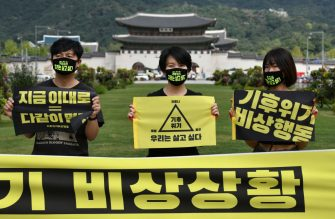 """South Korean environmental activists hold signs reading """"Climate crisis, We want to live"""" during a protest marking a global climate action day in Seoul on September 25, 2020. (Photo by Jung Yeon-je / AFP) (Photo by JUNG YEON-JE/AFP via Getty Images)"""