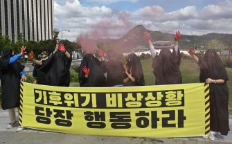 South Korean environmental activists wearing black cloth perform to represent the burning earth during a protest marking a global climate action day in Seoul on September 25, 2020. (Photo by Jung Yeon-je / AFP) (Photo by JUNG YEON-JE/AFP via Getty Images)
