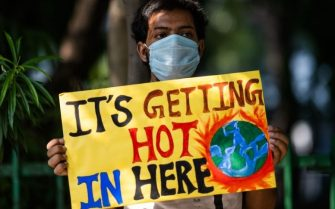 """A participant displays a placard during a demonstration as a part of the """"Fridays for Future"""" movement in New Delhi on September 25, 2020. (Photo by Jewel SAMAD / AFP) (Photo by JEWEL SAMAD/AFP via Getty Images)"""