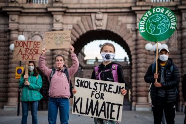 """Swedish climate activist Greta Thunberg holds a sign reading """"School strike for Climate"""" as she takes part in a protest in front of the Swedish Parliament (Riksdagen) in Stockholm on September 25, 2020. (Photo by JONATHAN NACKSTRAND / AFP) (Photo by JONATHAN NACKSTRAND/AFP via Getty Images)"""