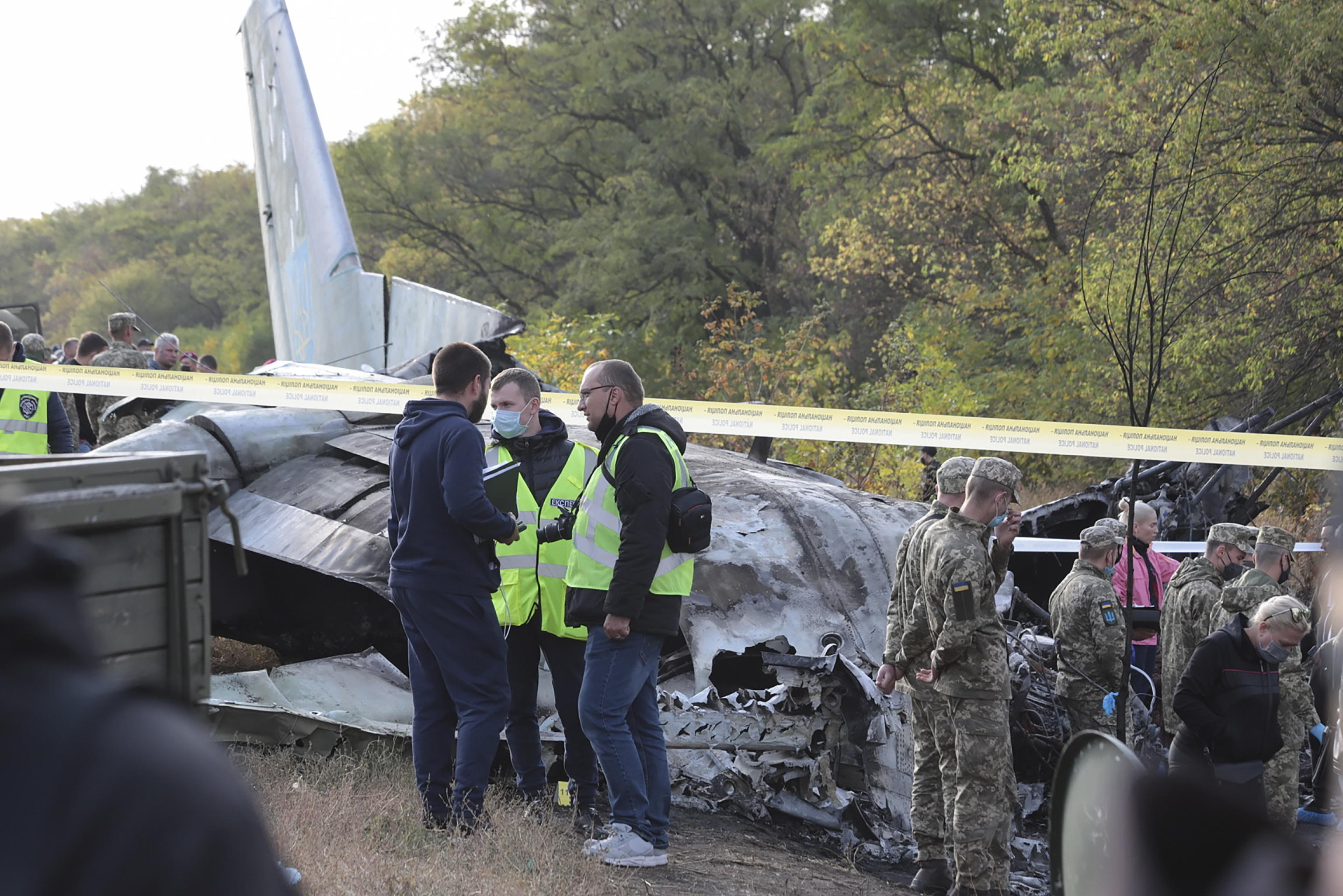epa08698267 Rescuers inspect the crash site of the An-26 plane near of Chuguev city of Kharkiv's area, Ukraine, 26 September 2020. The An-26 plane of the Ukrainian Air Force crashed while landing at the Chuguev airport in Kharkiv region. Asides from the crew, 21 cadets of the Kharkiv National University of the Air Force were on board because it was a training flight according to preliminary information. A fire broke out during the plane crash. 22 people were killed, two were injured. A total of 28 persons were on board as local media report.  EPA/SERGEY KHRUPOV