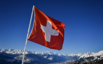 """A Swiss flag flutters on March 4, 2018 in Crans-Montana above the Rhone valley in the Swiss canton of Valais, location of Sion, a city of some 34,000 souls bidding to host the 2026 Winter Olympic Games. - The official race to succeed 2018 hosts Pyeongchang, and Beijing in 2022 begins in March when would be candidates file """"letters of intention"""" to the International Olympic Committee. (Photo by Fabrice COFFRINI / AFP) (Photo by FABRICE COFFRINI/AFP via Getty Images)"""