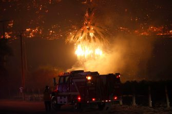 epa08702846 A palm tree burnst into flames near a fire engine as the Glass Fire burns near the town of Deer Park in Napa County, California, USA, 27 September 2020. Northern California is under extreme fire alert.  EPA/JOHN G. MABANGLO