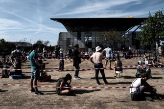 TOPSHOT - People sit on the ground as they queue to get tested for Covid-19, on September 11, 2020 in Venissieux, near Lyon, amid the novel coronavirus pandemic. (Photo by JEFF PACHOUD / AFP) (Photo by JEFF PACHOUD/AFP via Getty Images)