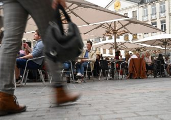 A woman walks by as clients sit at a cafe's terrace on September 9, 2020 in Lille, northern France. - From this Monday evening and for a fortnight, restaurants, night grocery stores, and bars will close at 12:30 a.m. every day in Lille to prevent the spread of the covid-19 pandemic caused  by the novel coronavirus. (Photo by DENIS CHARLET / AFP) (Photo by DENIS CHARLET/AFP via Getty Images)