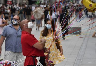 People with protective mask walk past a balloons street seller on a pedestrian street in Lyon on August 22, 2020 on the first day of mandatory mask wearing in parts of city centre. - Masks are obligatory to curb the spread of COVID-19 disease caused by the novel coronavirus in France in open areas of some cities as well as on public transport and in enclosed spaces such as shops, banks and government offices. (Photo by PHILIPPE DESMAZES / AFP) (Photo by PHILIPPE DESMAZES/AFP via Getty Images)