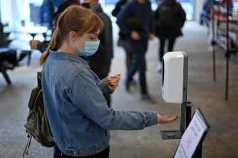 A woman wearing a protective face mask uses a hand sanitiser in The Old Truman Brewery's markets in east London on September 26, 2020, as Londoners live with new restrictions, introduced to combat the spread of the novel coronavirus pandemic. - Britain has tightened restrictions to stem a surge of coronavirus cases, ordering pubs to close early and advising people to go back to working from home to prevent a second national lockdown. (Photo by DANIEL LEAL-OLIVAS / AFP) (Photo by DANIEL LEAL-OLIVAS/AFP via Getty Images)