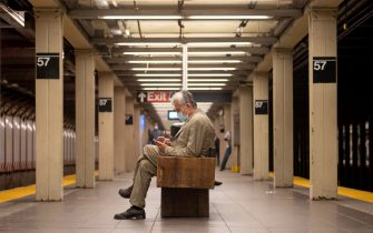 NEW YORK, NEW YORK - SEPTEMBER 29: A man wearing a mask looks at his phone while sitting in the 57th Street subway station as the city continues Phase 4 of re-opening following restrictions imposed to slow the spread of coronavirus on September 29, 2020 in New York City. The fourth phase allows outdoor arts and entertainment, sporting events without fans and media production. (Photo by Alexi Rosenfeld/Getty Images)