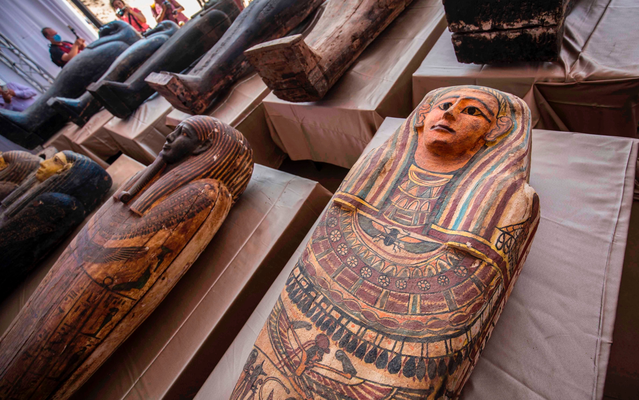 A picture taken on October 3, 2020 shows sarcophaguses, excavated by the Egyptian archaeological mission which discovered a deep burial well with more than 59 human coffins closed for more than 2,500 years, displayed during a press conference  at the Saqqara necropolis, 30 kms south of the Egyptian capital Cairo. - They were unearthed south of Cairo in the sprawling burial ground of Saqqara, the necropolis of the ancient Egyptian capital of Memphis, a UNESCO World Heritage site. Their exteriors are covered in intricate designs in vibrant colours as well as hieroglyphic pictorials. (Photo by Khaled DESOUKI / AFP) (Photo by KHALED DESOUKI/AFP via Getty Images)