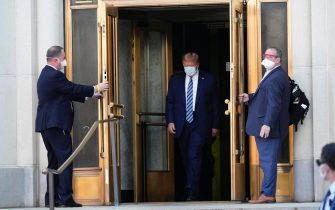 epa08723008 US President Donald J. Trump, wearing a mask, emerges from the front door of Walter Reed National Military Medical Center, in Bethesda, Maryland, USA, 05 October 2020, to board Marine One for a return trip to the White House after receiving treatment for a COVID-19 infection.  EPA/Chris Kleponis / POOL