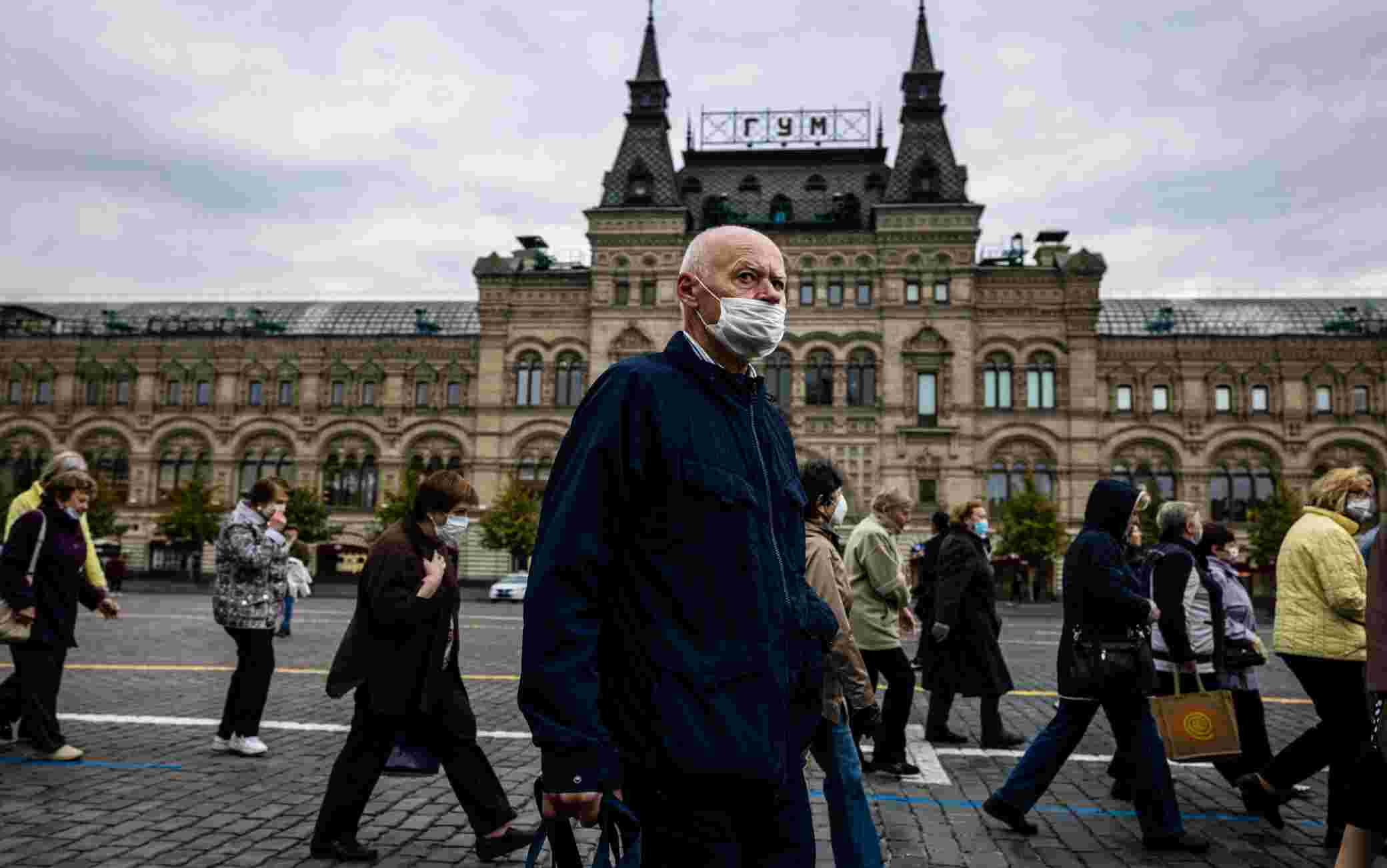 A man wearing a face mask to protect against the coronavirus disease walks on Red Square in front of the GUM department store in central Moscow on October 7, 2020. (Photo by Dimitar DILKOFF / AFP) (Photo by DIMITAR DILKOFF/AFP via Getty Images)