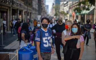 MEXICO CITY, MEXICO - OCTOBER 08: People look on while wearing face masks on October 08, 2020 in Mexico City, Mexico. Mexico City is the area worst hit by COVID-19 in the country. Still 158 neighborhoods remain under red alert and their number of active positive cases represents 33% of city total. These areas are being prioritized for medical attention and economic aid programs. Since the beginning of the pandemic in March, the country registered 800,000 positive cases of COVID-19 and over 82,000 related deaths. (Photo by Hector Vivas/Getty Images)
