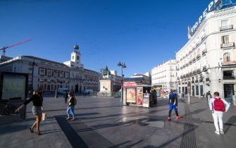 People transit during the day following the lifting of the confinement by court order at Puerta del Sol on October 9, 2020 in Madrid, Spain.
