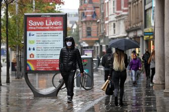 """A man wearing a protective face mask passes a board displaying information how to restrict the spread of coronavirus covid-19, in central Nottingham in central England on October 9, 2020. - Pubs and restaurants in coronavirus hotspots look set to face fresh restrictions after Downing Street said new data suggests there is """"significant"""" transmission taking place in hospitality settings. A """"range of measures"""" is being looked at, with a particular focus on northern England, where it says infection rates are rising fastest. (Photo by Oli SCARFF / AFP) (Photo by OLI SCARFF/AFP via Getty Images)"""