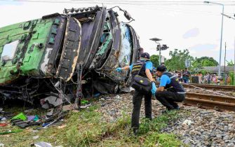 Investigators work by the wreckage of an overturned bus involved in a deadly collision with a train next to Khlong Kwaeng Klan railway station in Chachoengsao province, east of the Thai capital Bangkok, on October 11, 2020. (Photo by Mladen ANTONOV / AFP) (Photo by MLADEN ANTONOV/AFP via Getty Images)