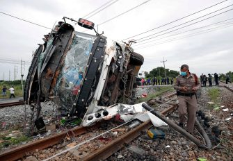 epa08735137 Thai police officer inspects a wreckage bus after it collided with a train at Khlong Kwaeng Klan railway station in Chachoengsao province, Thailand, 11 October 2020. Twenty people were killed while another 30 injured after a train crashed into a bus carrying Buddhist devotees heading to a temple for a merit making ceremony to mark the end of Buddhist Lent, police said.  EPA/RUNGROJ YONGRIT