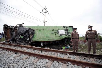 epa08735138 Thai police officers inspect a wreckage bus after it collided with a train at Khlong Kwaeng Klan railway station in Chachoengsao province, Thailand, 11 October 2020. Twenty people were killed while another 30 injured after a train crashed into a bus carrying Buddhist devotees heading to a temple for a merit making ceremony to mark the end of Buddhist Lent, police said.  EPA/RUNGROJ YONGRIT