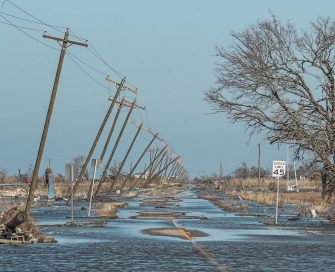 epa08735054 Utility poles lean along a flooded road in Cameron, Louisiana, USA, 10 October 2020.  Hurricane Delta came ashore nearby causing widespread damage and power outages to hundreds of thousands of people in Louisiana, Texas and Mississippi just six weeks after Hurricane Laura caused wiidespread damage.  EPA/TANNEN MAURY