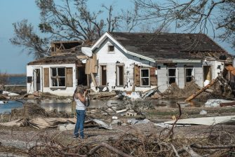 epa08735050 A woman photographs damaged property in Cameron, Louisiana, USA, 10 October 2020. Hurricane Delta came ashore nearby causing widespread damage and power outages to hundreds of thousands of people in Louisiana, Texas and Mississippi just six weeks after Hurricane Laura caused wiidespread damage.  EPA/TANNEN MAURY