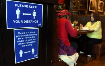"""A sign outlining social distancing is displayed near customers in Jackson's Bar in the city centre of Glasgow on October 8, 2020, on the eve of a two-week closure of pubs due to an increase in the number of cases of the novel coronavirus COVID-19. - Scotland, on October 7, 2020, ordered a two-week closure of pubs in the central part of the country including the main cities Glasgow and Edinburgh.  First Minister Nicola Sturgeon said the measures, to last for 16 days from October 9, were designed as """"short, sharp action to arrest the worrying increase in infection"""". (Photo by Andy Buchanan / AFP) (Photo by ANDY BUCHANAN/AFP via Getty Images)"""