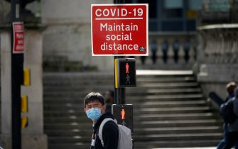 LIVERPOOL, ENGLAND - OCTOBER 08: A social distancing sign is affixed next to a pedestrian crossing on October 08, 2020 in Liverpool, England. It has been reported that a three-tier lockdown system, similar to a traffic light system is being contemplated by the British government to simplify coronavirus (Covid-19) lockdown measures. (Photo by Christopher Furlong/Getty Images)