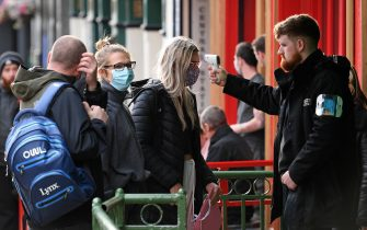 A security guard uses a handheld thermometer to take the temperature of customers, wearing face masks or coverings due to the COVID-19 pandemic, as they wait to enter a bar in Liverpool, north west England on October 2, 2020, following the  announcement of new local restrictions for certain areas in the northwest of the country, due to a resurgence of novel coronavirus cases. - The British government on Thursday extended lockdowns to Liverpool and several other towns in northern England, effectively putting more than a quarter of the country under tighter coronavirus restrictions. Health Secretary Matt Hancock said limits on social gatherings would be extended to the Liverpool City region, which has a population of about 1.5 million. (Photo by Oli SCARFF / AFP) (Photo by OLI SCARFF/AFP via Getty Images)