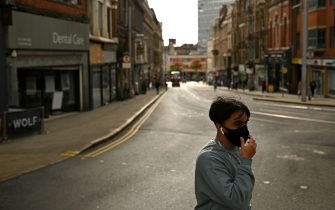 """A pedestrian wearing a protective face covering to restrict the spread of coronavirus covid-19 crosses a street in central Nottingham in central England on October 9, 2020. - Pubs and restaurants in coronavirus hotspots look set to face fresh restrictions after Downing Street said new data suggests there is """"significant"""" transmission taking place in hospitality settings. A """"range of measures"""" is being looked at, with a particular focus on northern England, where it says infection rates are rising fastest. (Photo by Oli SCARFF / AFP) (Photo by OLI SCARFF/AFP via Getty Images)"""