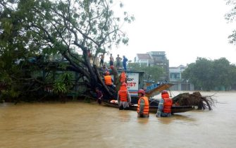 epa08739573 Municipal workers evacuate local people from flood water in Hue, Vietnam, 13 October 2020. Heavy rains and floods killed at least 23 people in northern and central Vietnam during the past few days, according to media reports.  EPA/STR VIETNAM OUT