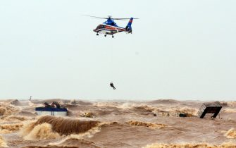 epa08735553 A helicopter from Ministry of Defence rescue stranded crew members at the sea, in Quang Tri province, Vietnam, 11 October 2020. Heavy rains and floods killed nine people and left 11 missing in northern and central Vietnam during the past few days, according to media reports.  EPA/STR VIETNAM OUT