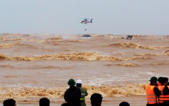 epa08735554 A helicopter from Ministry of Defence rescue stranded crew members at the sea, in Quang Tri province, Vietnam, 11 October 2020. Heavy rains and floods killed nine people and left 11 missing in northern and central Vietnam during the past few days, according to media reports.  EPA/STR VIETNAM OUT