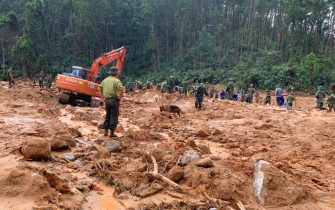 Rescue workers recover bodies of army officers buried in a landslide in Thua Thien-Hue province, Vietnam on Thursday, Oct. 15, 2020. Rescuers has recovered 13 bodies from a landslide due to torrential rains that flooded a vast area in central Vietnam and killed at least 36 people, left a dozen others still missing since last weekend. (Tran Le Lam/VNA via AP)