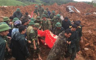 Army officers carry a body recovered from a landslide in Quang Tri province, Vietnam on Sunday, Oct. 18, 2020. A landslide in central Vietnam buries at least 22 army officers, just a week after another landslide killed 13 others due to prolong rains in the region, state media reported. (Tran Le Lam/ VNA via AP)