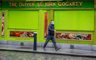 A pedestrian wearing a face mask or covering due to the COVID-19 pandemic, walks past a closed-down pub in Dublin on October 19, 2020, amid reports that further lockdown restrictions could be imposed to help mitigate the spread of the novel coronavirus. - Ireland will crank up coronavirus restrictions, prime minister Micheal Martin said last week, announcing a raft of new curbs along the border with the British province of Northern Ireland. (Photo by PAUL FAITH / AFP) (Photo by PAUL FAITH/AFP via Getty Images)