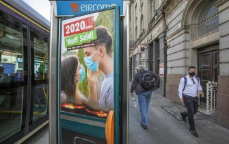 """A pedestrian wearing a face mask or covering due to the COVID-19 pandemic, walks past an advert depicting a young couple wearing facemasks, and the slogan """"2020, Nuff said!"""" in Dublin on September 18, 2020, amid reports that further lockdown restrictions could be imposed to help mitigate the spread of the novel coronavirus. - Ireland's capital could face further restrictions this weekend after public health experts raised concerns when its 14-day incidence rate jumped to more than 100. (Photo by Paul Faith / AFP) (Photo by PAUL FAITH/AFP via Getty Images)"""