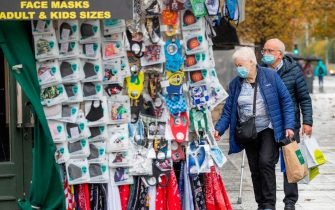 Pedestrians wearing face masks or coverings due to the COVID-19 pandemic, look a masks for sale in Dublin on October 19, 2020, amid reports that further lockdown restrictions could be imposed to help mitigate the spread of the novel coronavirus. - Ireland will crank up coronavirus restrictions, prime minister Micheal Martin said last week, announcing a raft of new curbs along the border with the British province of Northern Ireland. (Photo by PAUL FAITH / AFP) (Photo by PAUL FAITH/AFP via Getty Images)