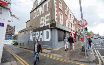"""A pedestrian walks past a mural reading """"Don't Be Afraid"""" in Dublin on October 19, 2020, amid reports that further lockdown restrictions could be imposed to help mitigate the spread of the novel coronavirus. - Ireland will crank up coronavirus restrictions, prime minister Micheal Martin said last week, announcing a raft of new curbs along the border with the British province of Northern Ireland. (Photo by Paul Faith / AFP) (Photo by PAUL FAITH/AFP via Getty Images)"""